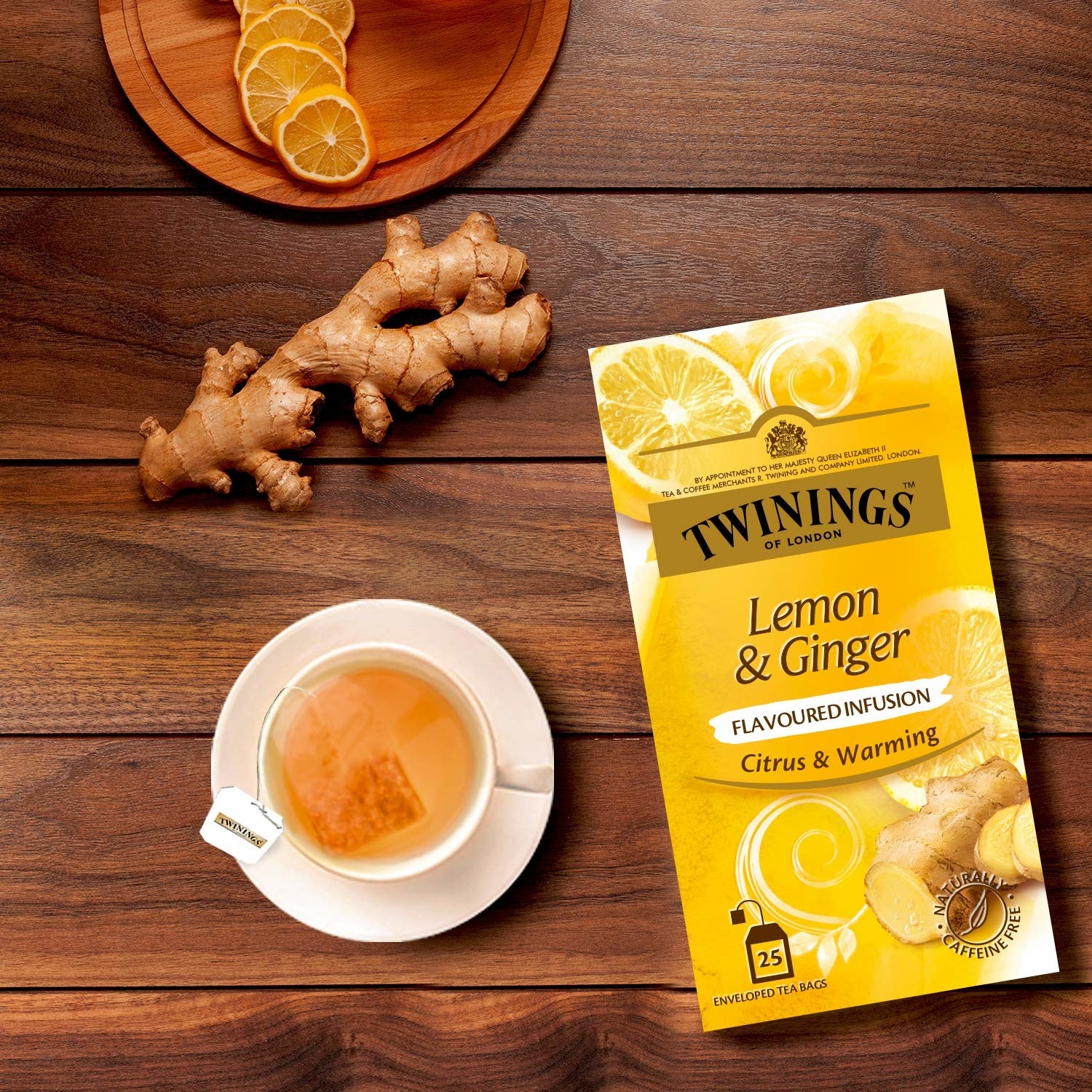 The box of tea placed next to lemon slices, some ginger, and a cup of tea