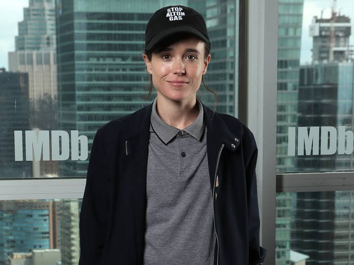Elliot smiles while wearing a baseball cap, grey polo and black zip up hoodie