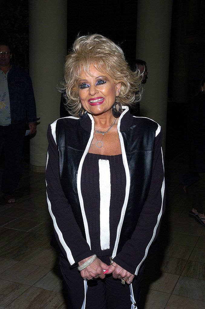 Tammy Faye Messner poses in a black and white outfit, bright lipstick, and heavy eye makeup