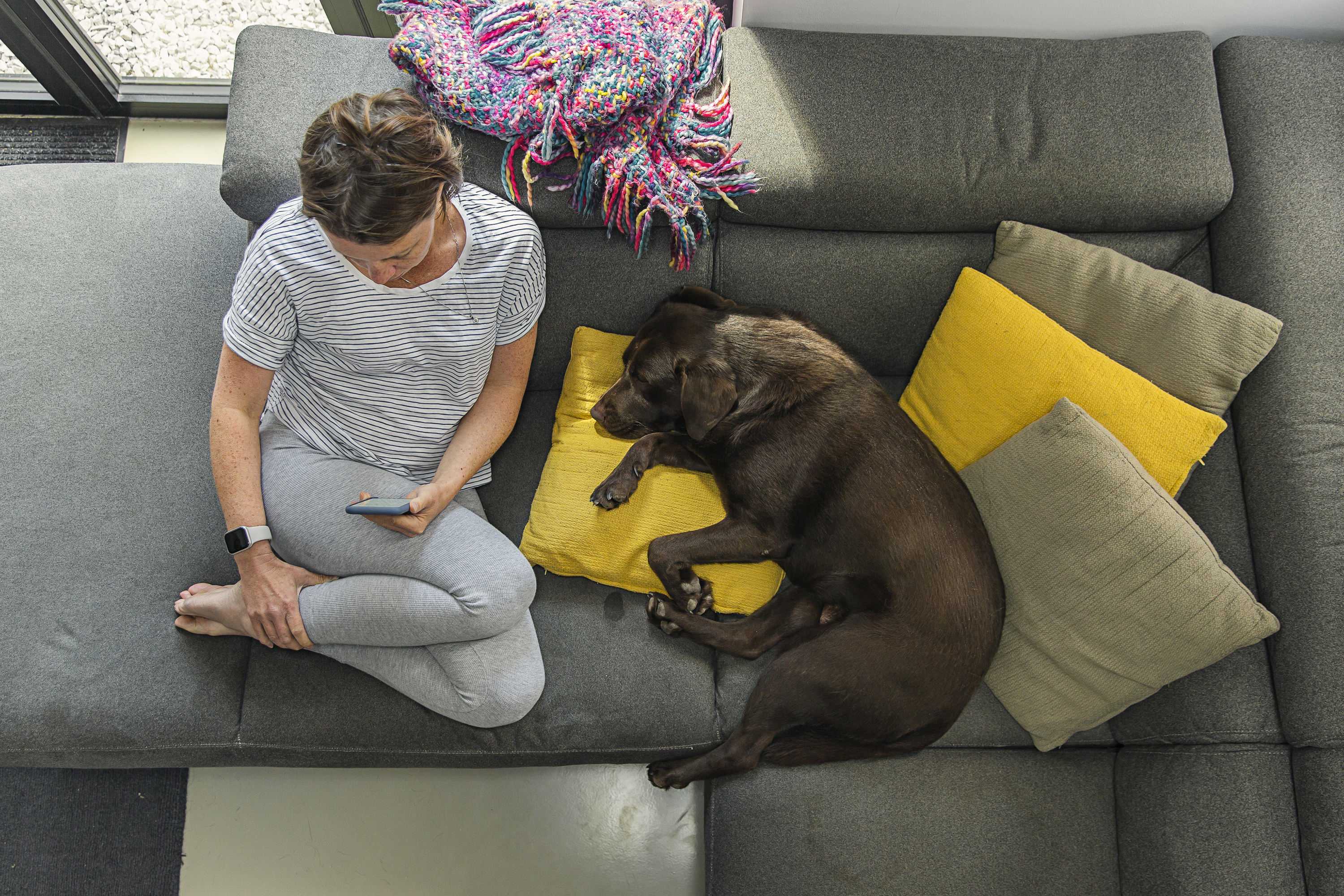 A woman sitting near a brown dog on a grey couch.