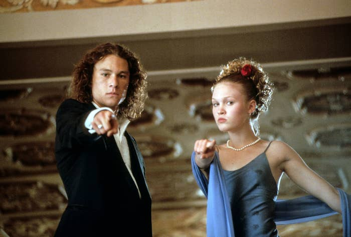 Heath Ledger and Julia Stiles in prom clothes point down at the camera