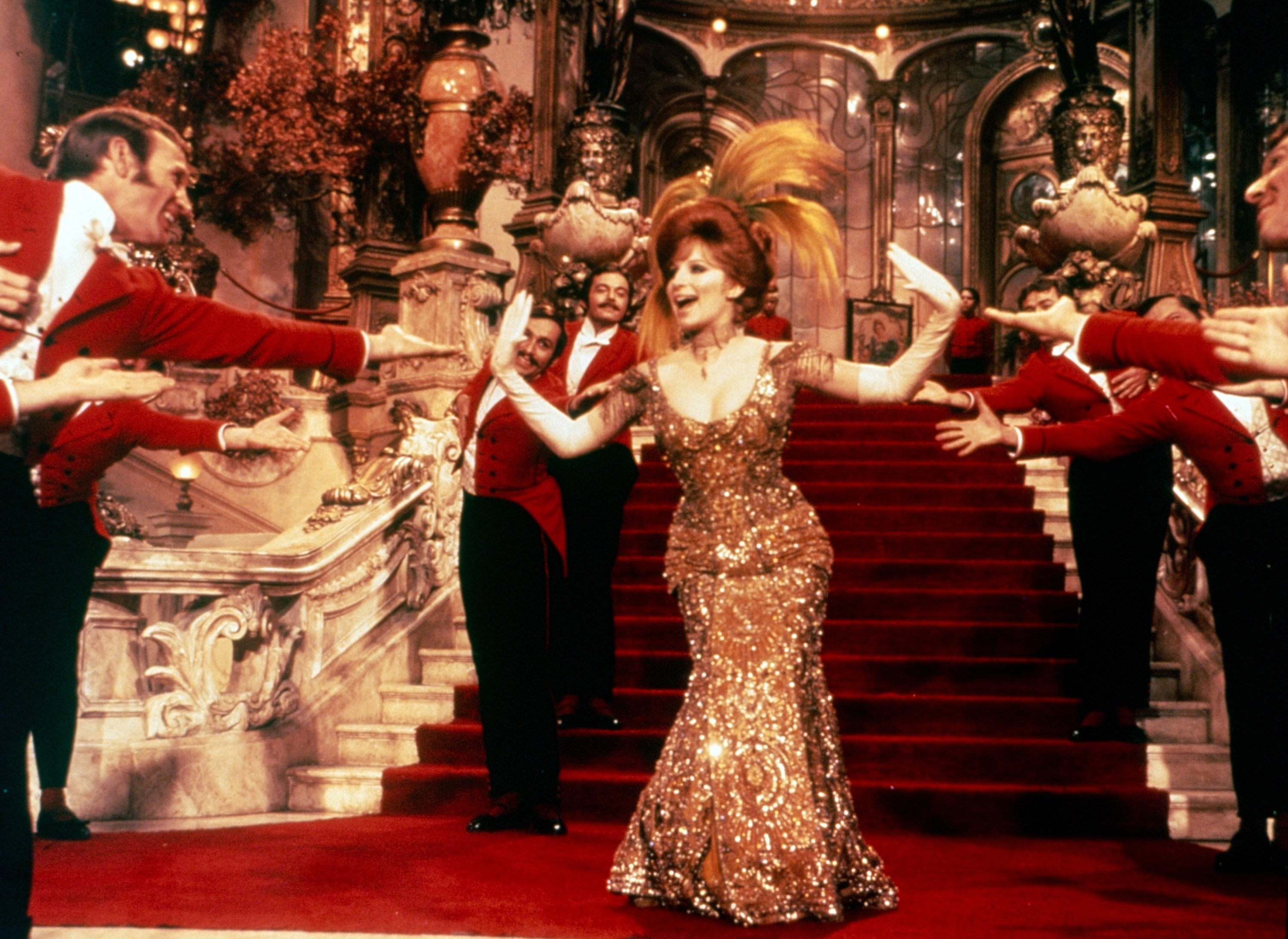 Barbra Streisand as Dolly sings in front of a large, red-carpeted staircase