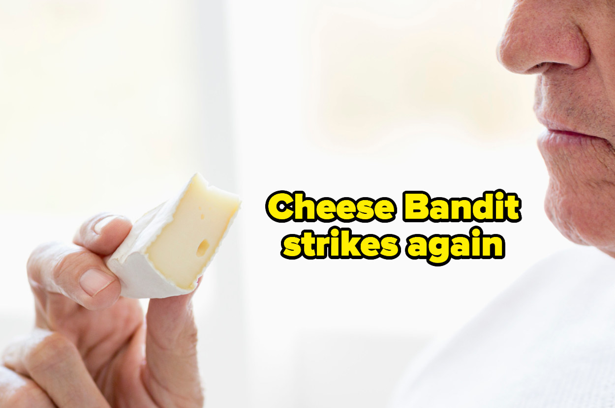 """man holding up a piece of cheese with """"Cheese Bandit strikes again"""""""