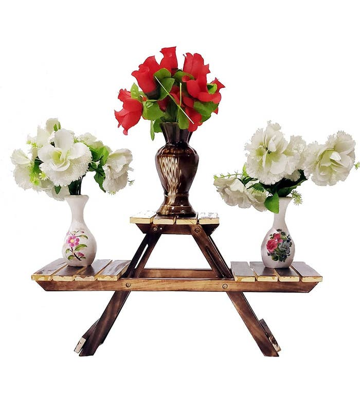 A wooden foldable stand with 3 racks holding flower vases