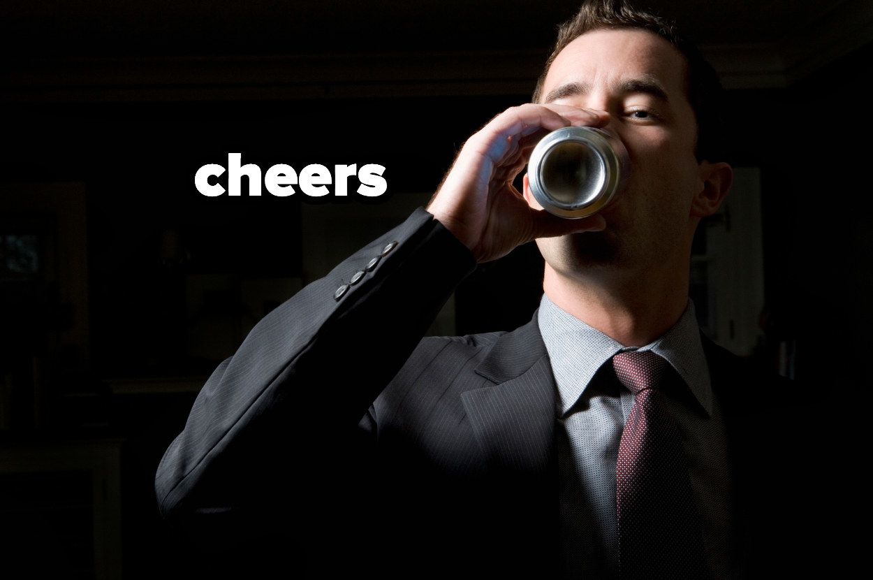 """man drinking a beer in a suit with """"cheers"""" by his head"""