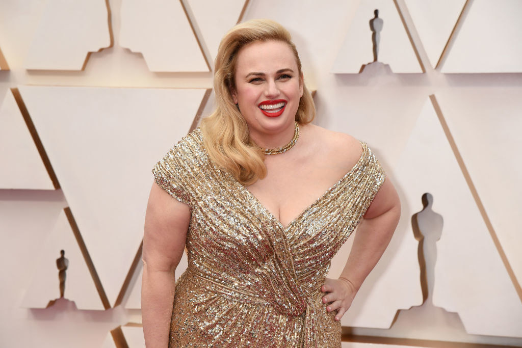 Rebel smiling on the Oscars red carpet in a sequined off-shoulder gown