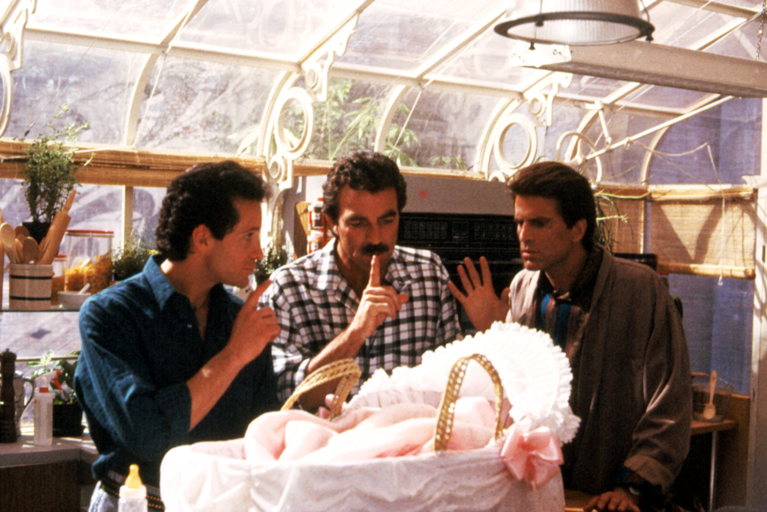 Steve Guttenberg, Tom Selleck, and Ted Danson huddle around a baby