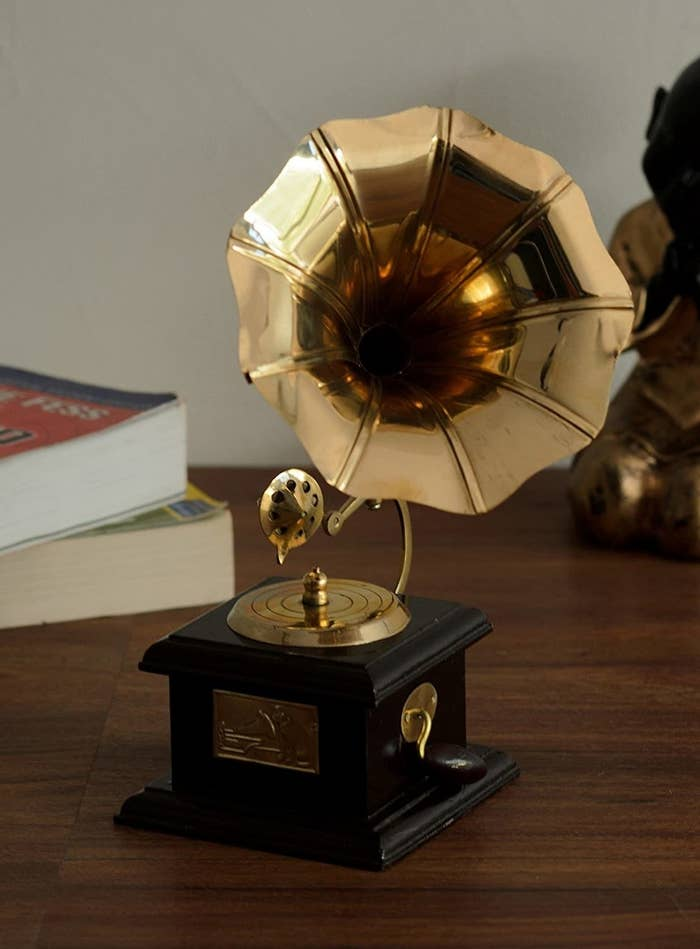 A brass gramophone showpiece with a wooden base and brass crank