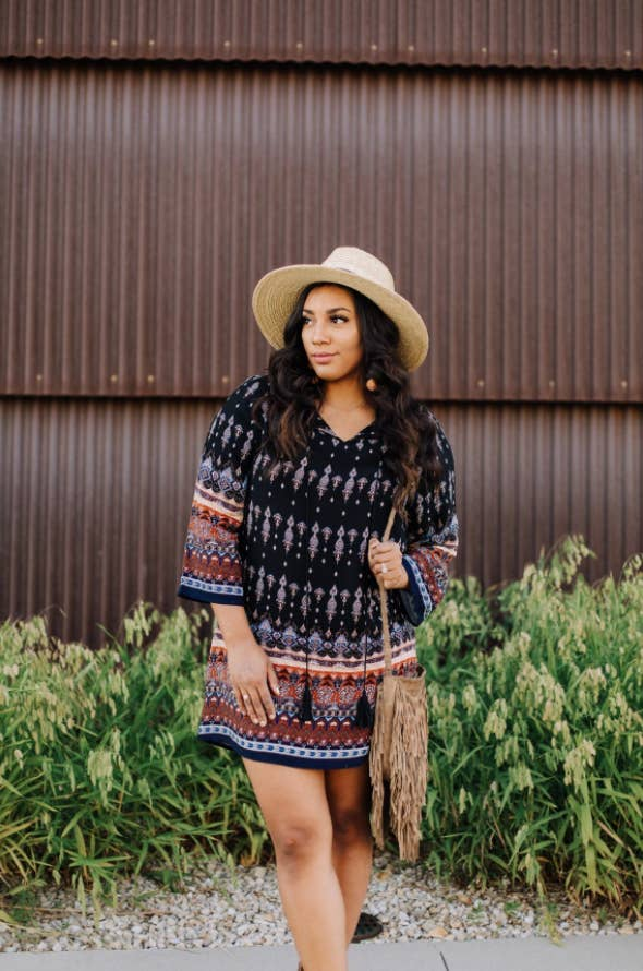 reviewer wearing long-sleeve midi in a boho-style print with bag and hat