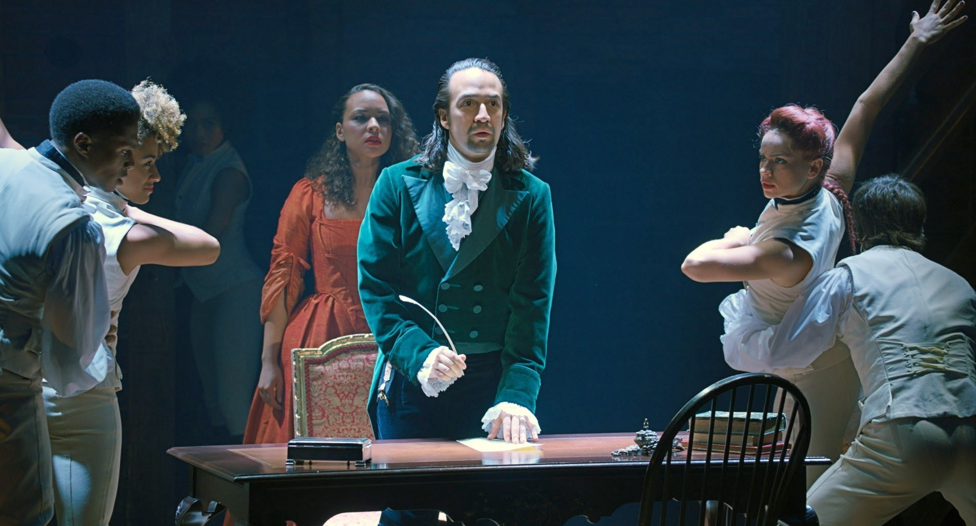 Lin-Manuel Miranda stands in front of a desk with a quill while dancers dance around him and Jasmine Cephas Jones sings behind him