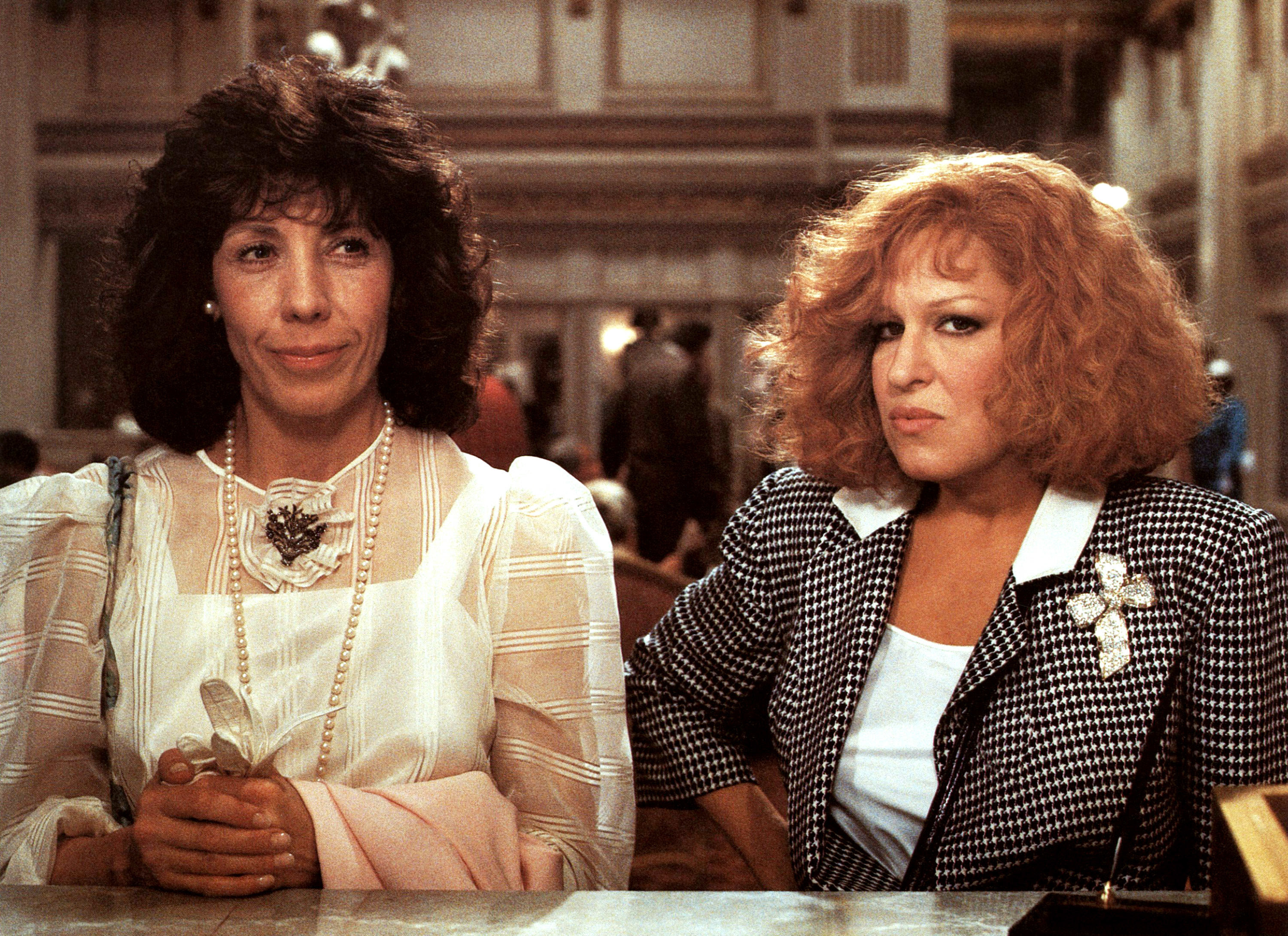 Lily Tomlin and Bette Midler stand at a counter