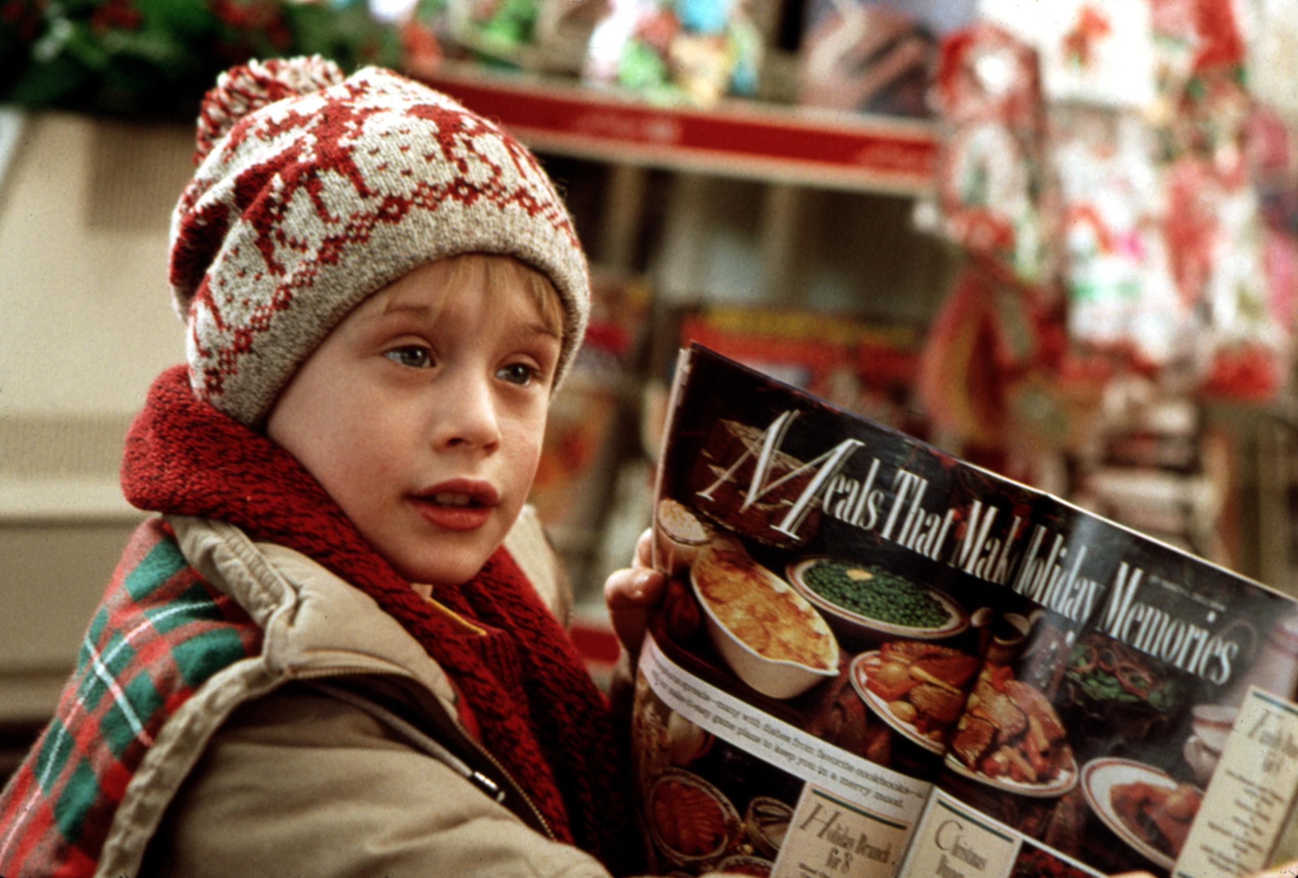 Macaulay Culkin looks at a magazine at a supermarket