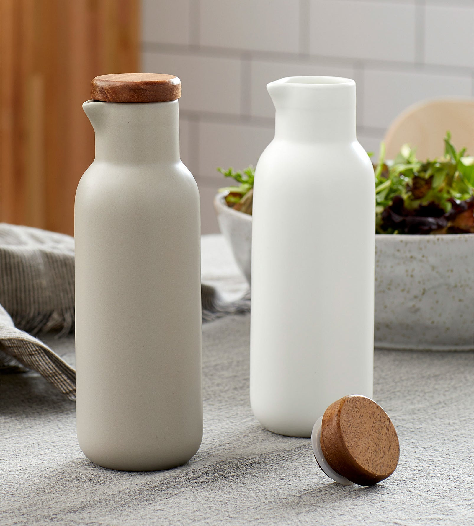 A pair of porcelain oil and vinegar bottles on a kitchen table