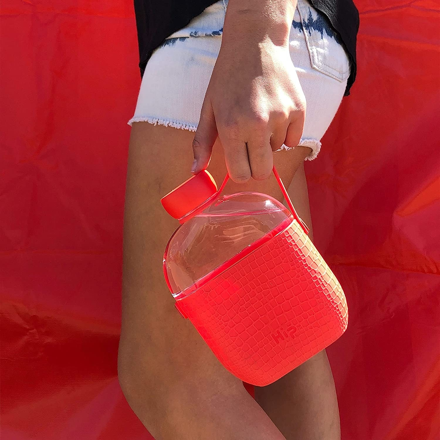 Someone carrying a flat water flask; the bottom half is covered in a silicone sleeve