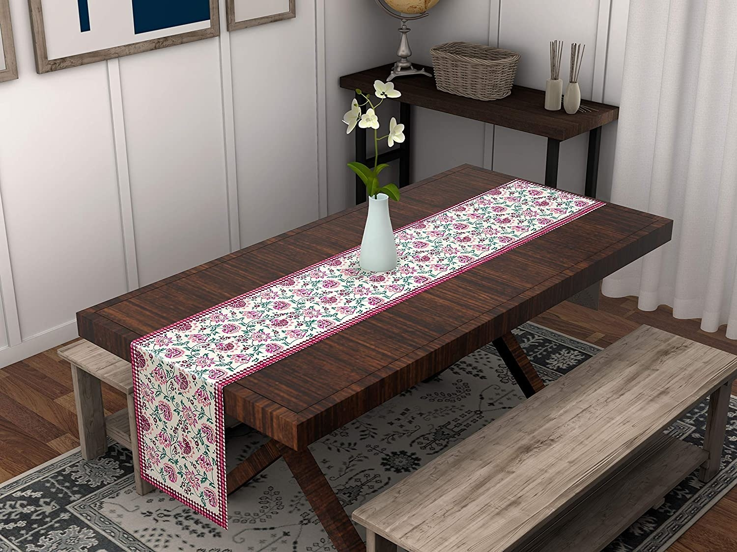 A white and pink table runner with flowers and leaves printed on it