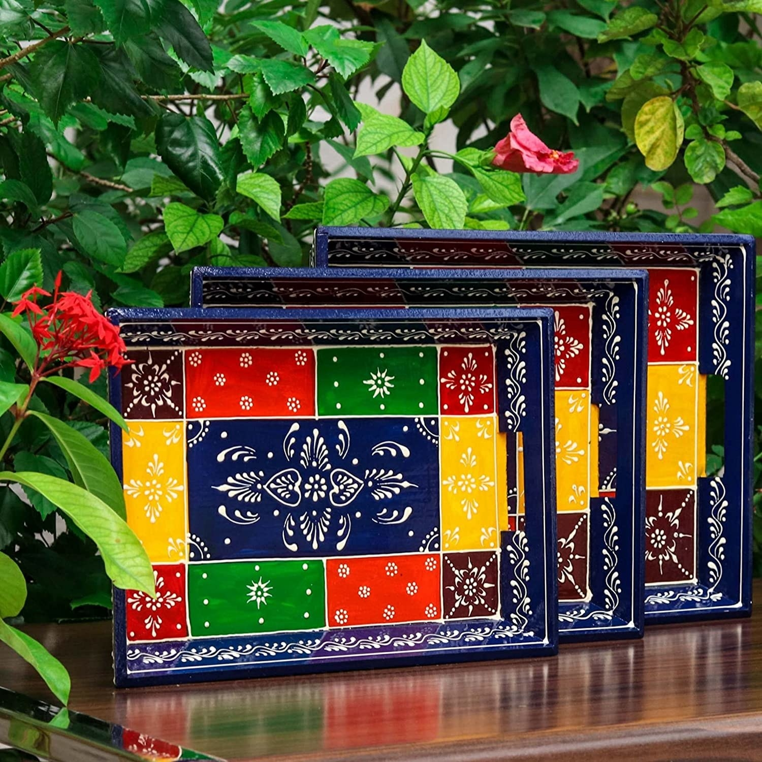 3 wooden serving trays with traditional designs and filled with different colours