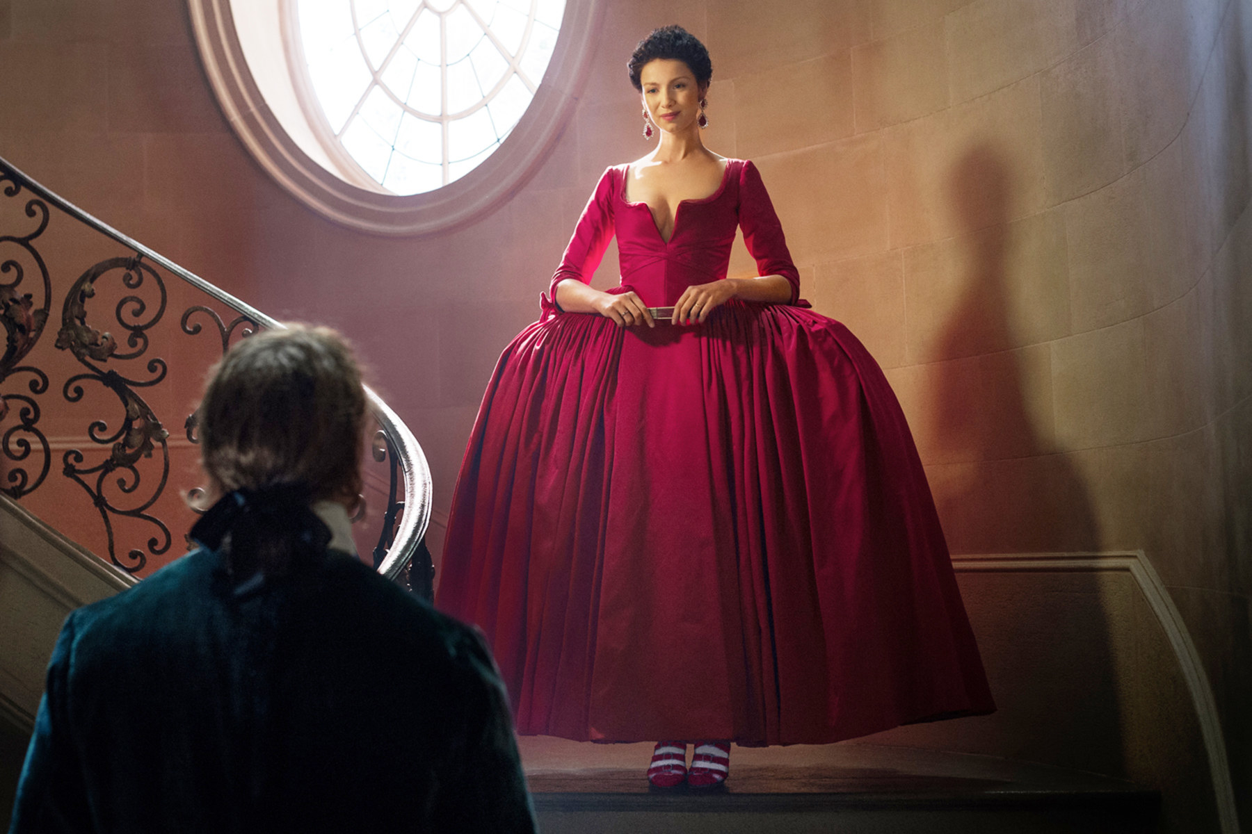 Jamie looking astonished at Claire as she descends down the stairs