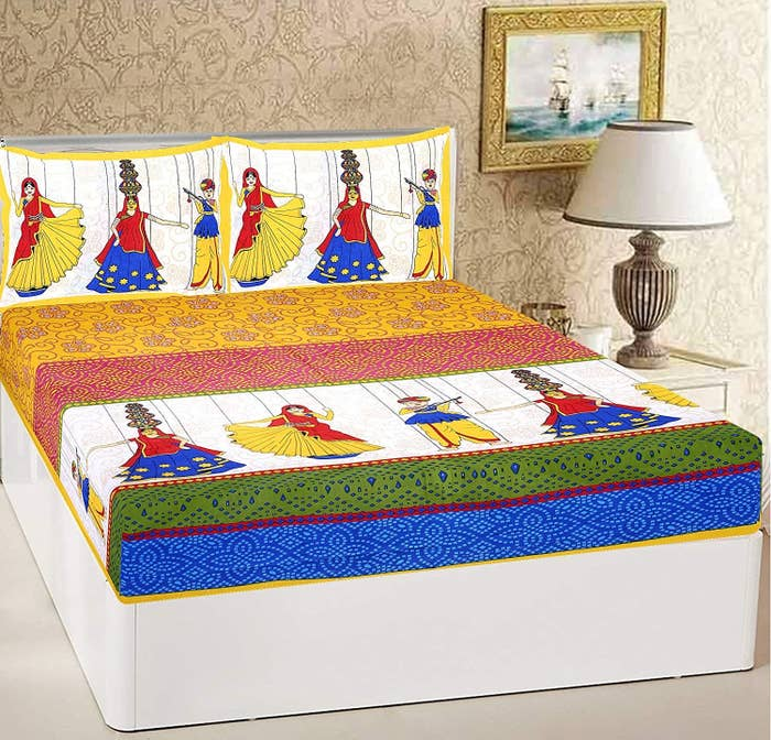 A colourful bed sheet with images of a man and woman dressed in traditional wear