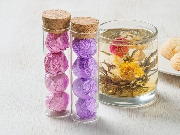 two containers with one filled with pink foil balls and the other with purple foil ball and a clear tea cup with tea and a blooming yellow flower inside