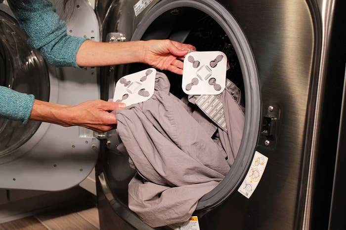 hands putting a sheet set with the white square devices hooked to the corners in a washer