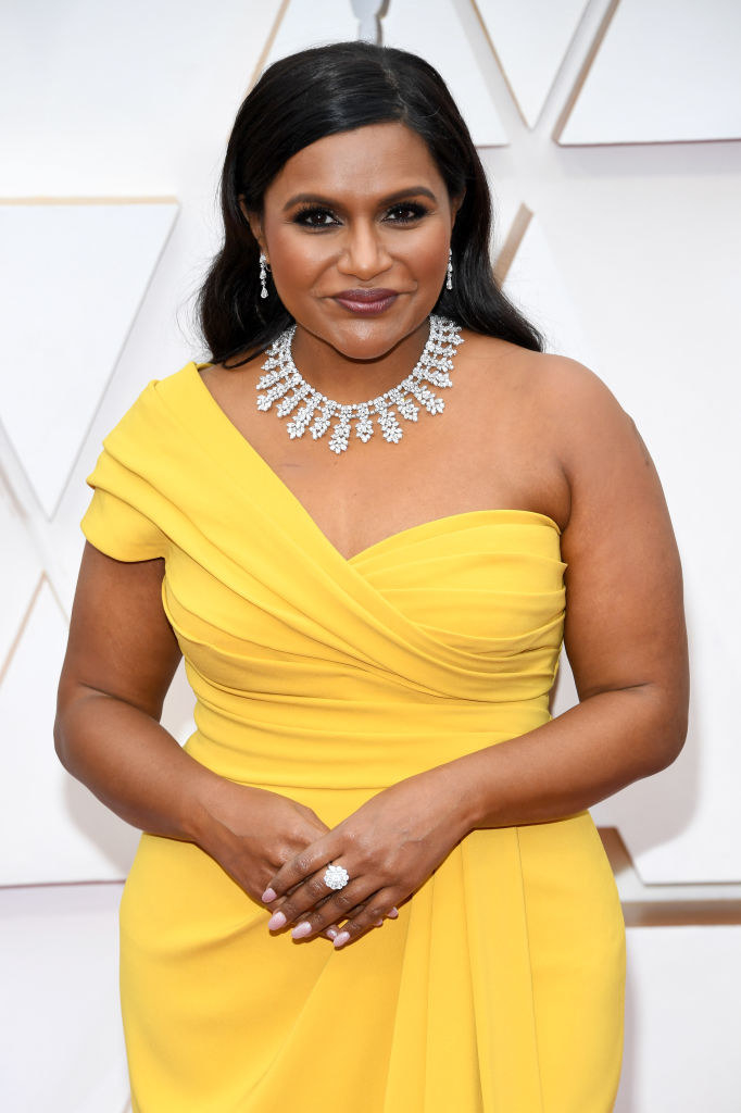 Mindy posing for photos on the red carpet in a bright one-shoulder gown and a diamond necklace