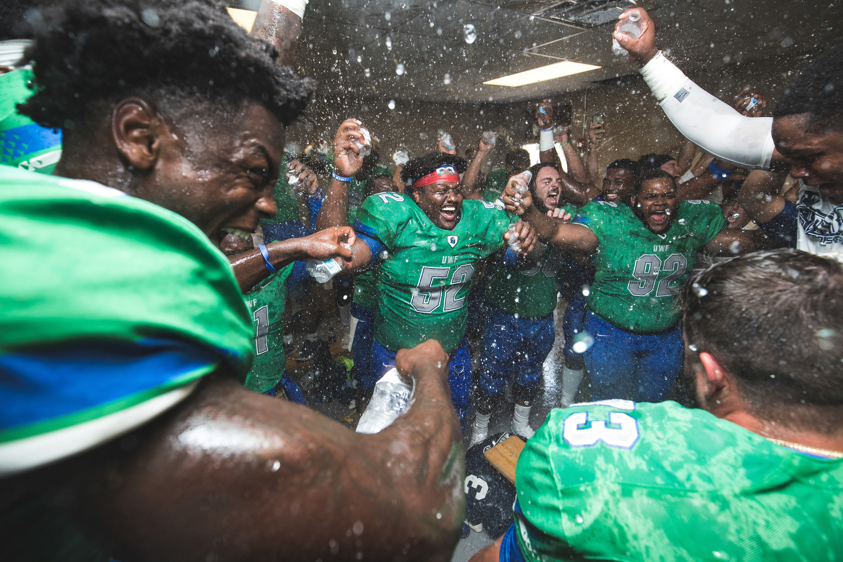 Football players celebrate a victory in their locker room after a game