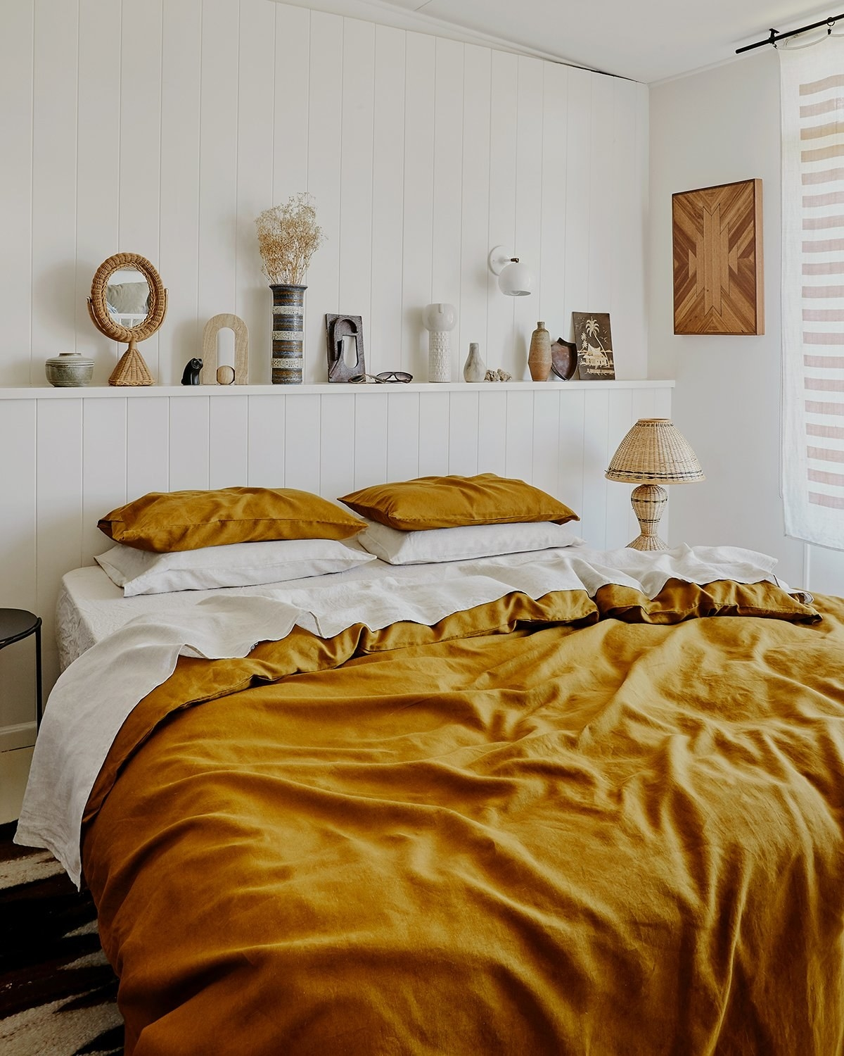 a beds with mustard yellow pillow cases and a linen comforter