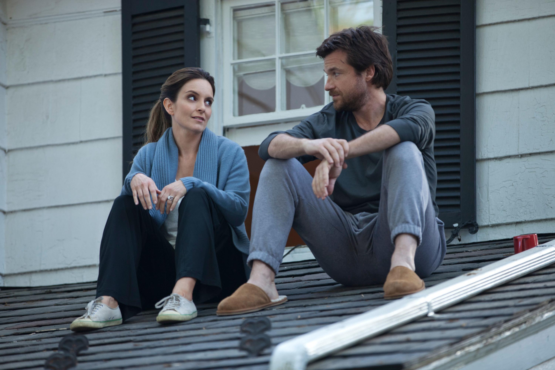 Tina Fey and Jason Bateman sitting on a roof.
