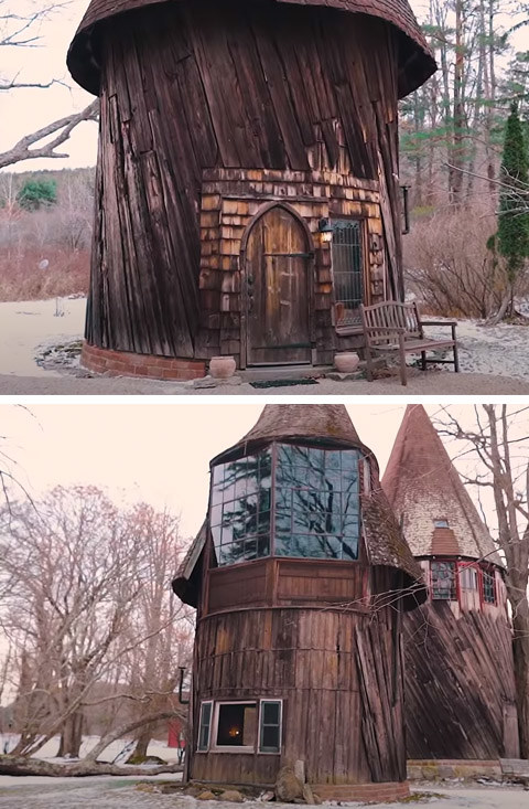 A tall wooden house with a pointy roof and a very rustic exterior