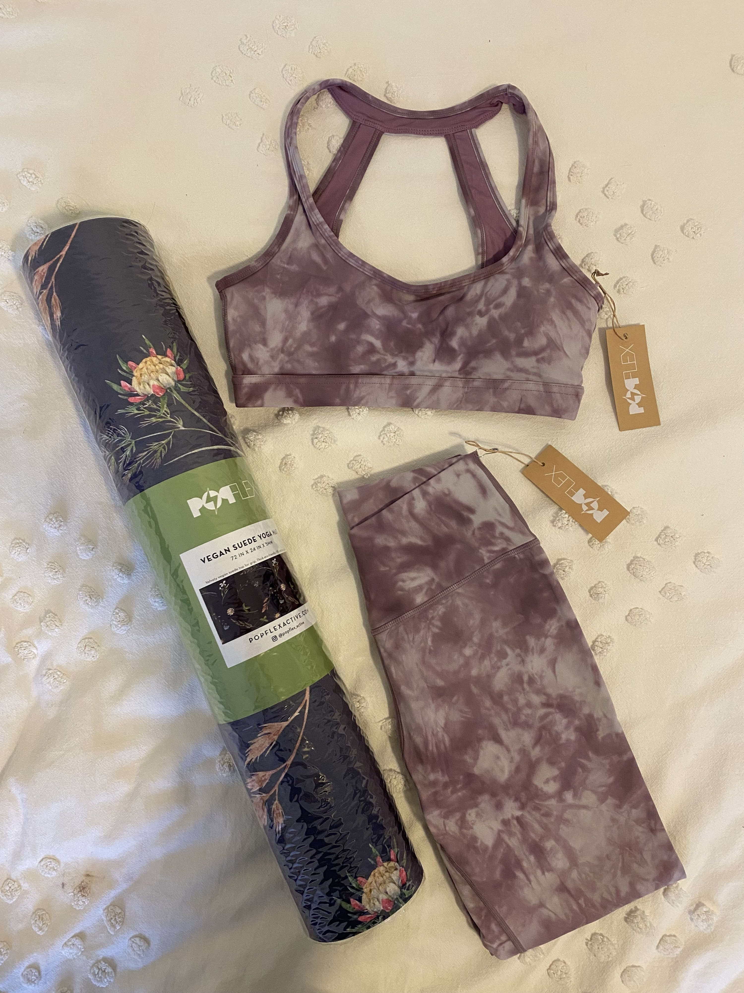 The yoga mat, sports bra, and leggings laid out on my bed