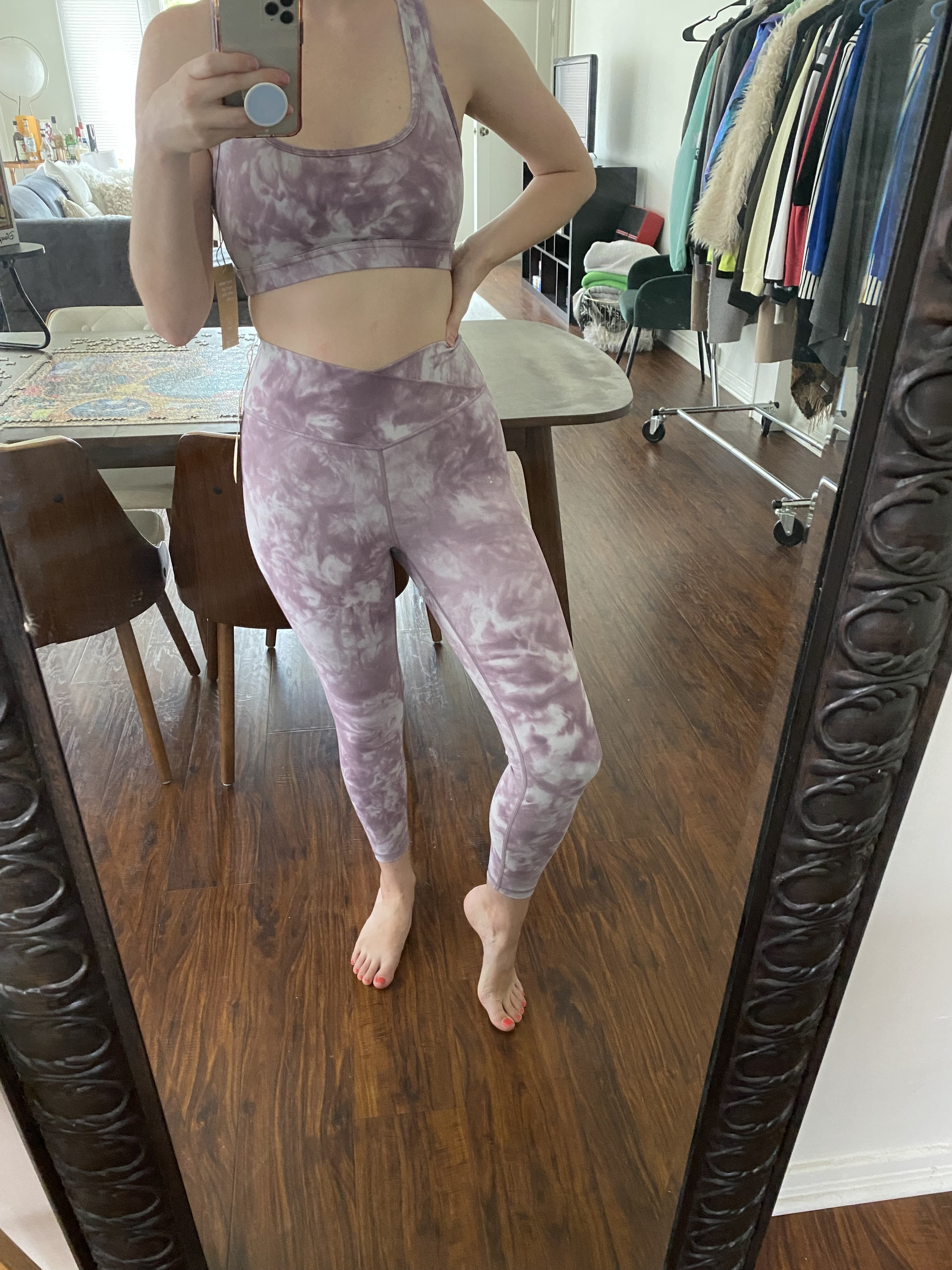 Me wearing the bra and leggings. The bra and leggings have a marble print, the sports bra is slightly low-cut with a large key hole cutout in the back, and the leggings come down to my ankles and have a crisscross waistband