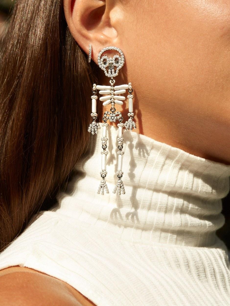 a big hanging earring shaped like a skeleton made of beads