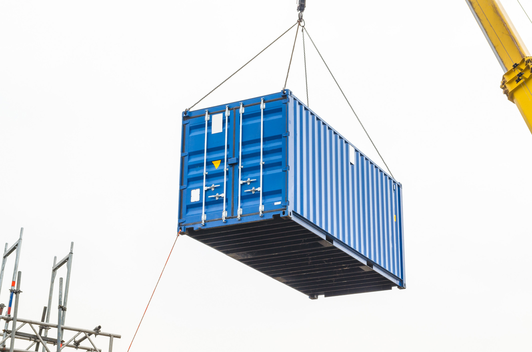 A typical shipping container being held up by a crane