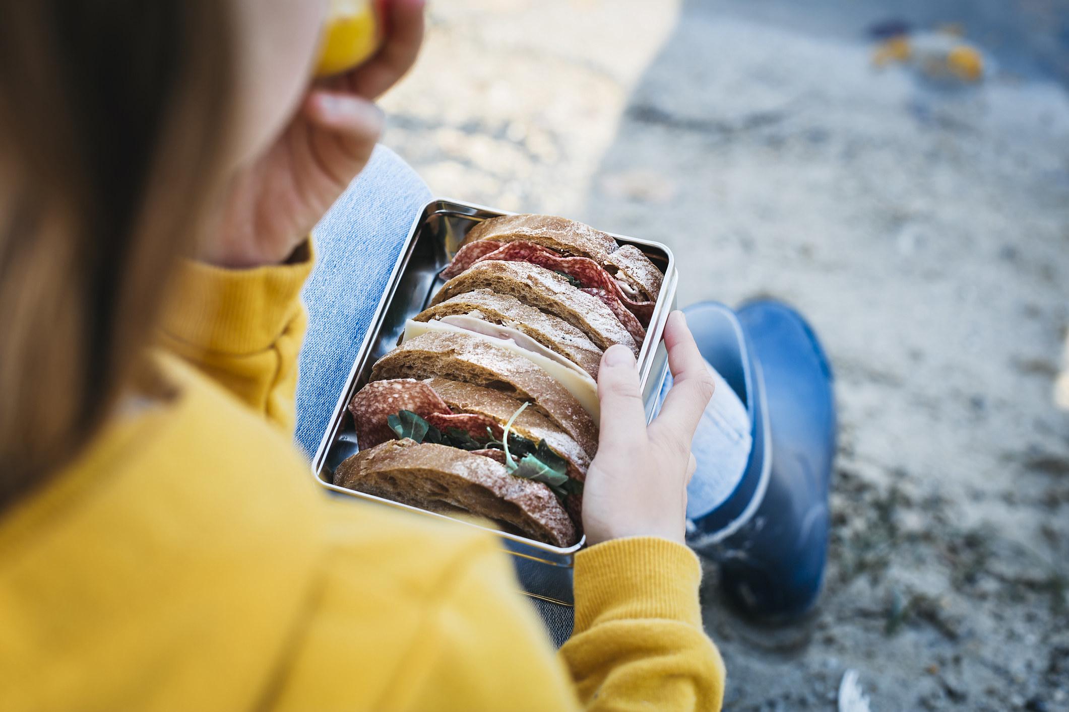 A woman eating a sandwich outside.