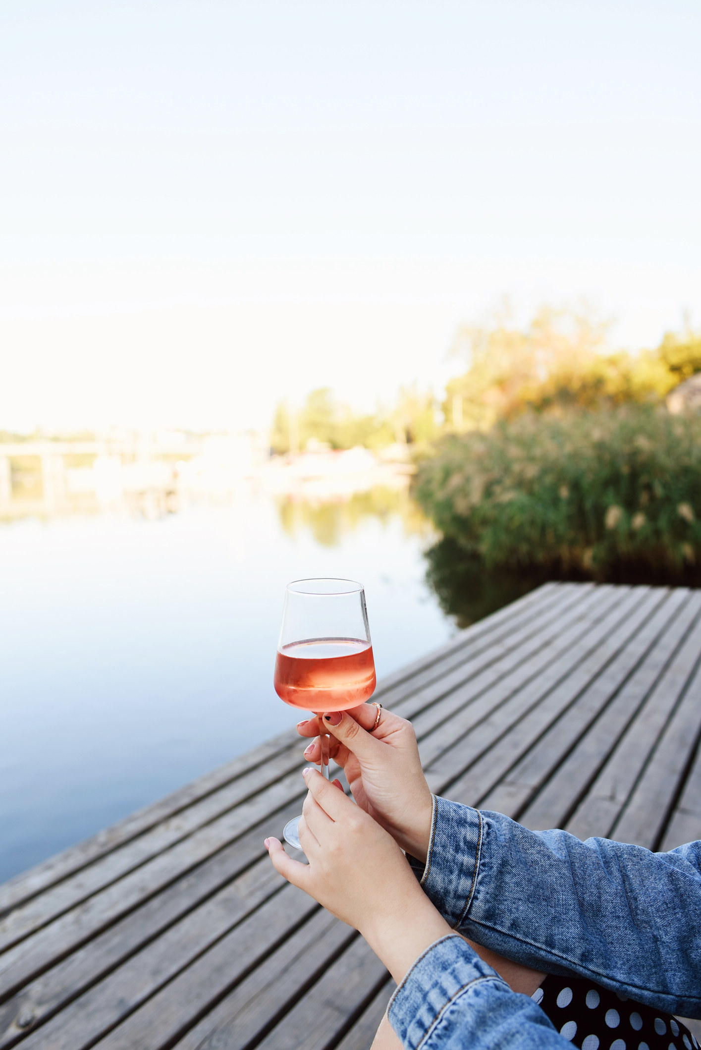Someone drinking a glass of rosé on a dock.