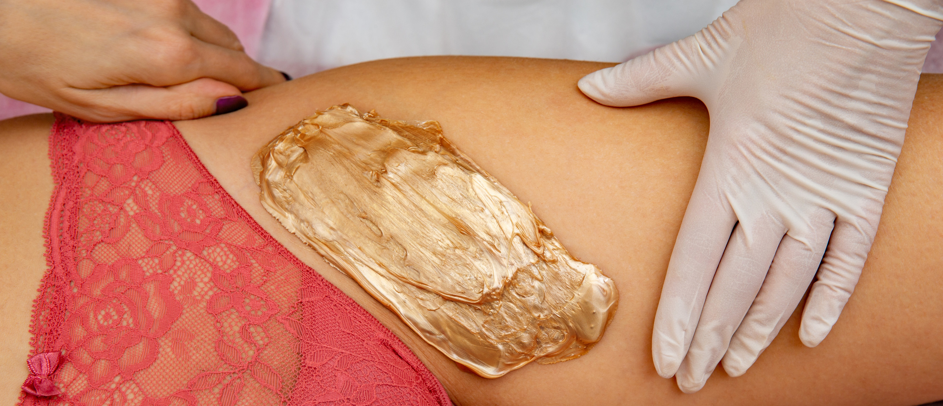 An image of a woman with wax near her genital area
