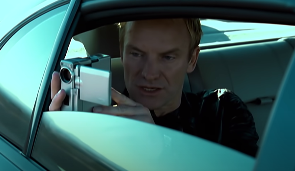 Screenshot of Sting in the back of a car filming with a video camera out the window