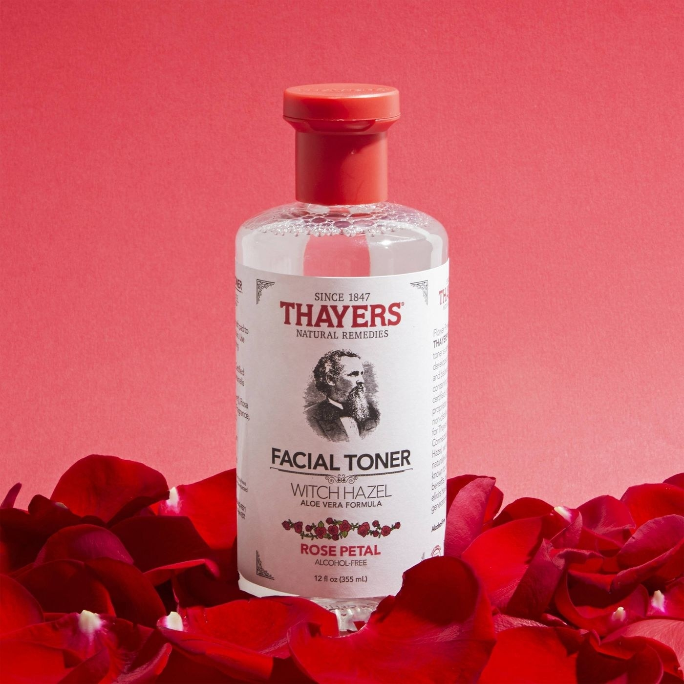 a bottle of rose petal witch hazel standing in red rose petals