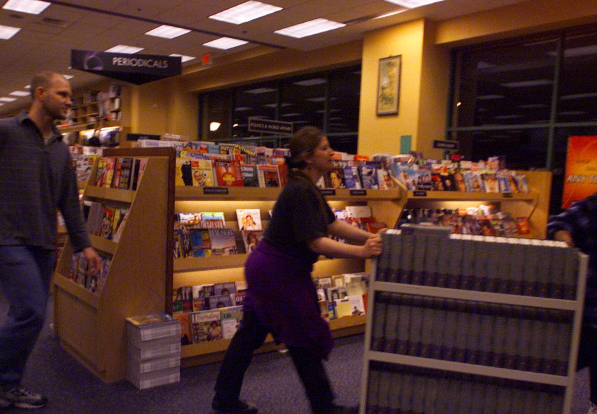 Workers pushing books with a magazine rack in the background