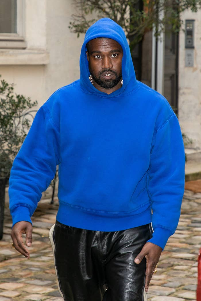 West walks down the street while wearing a hooded sweatshirt and leather pants