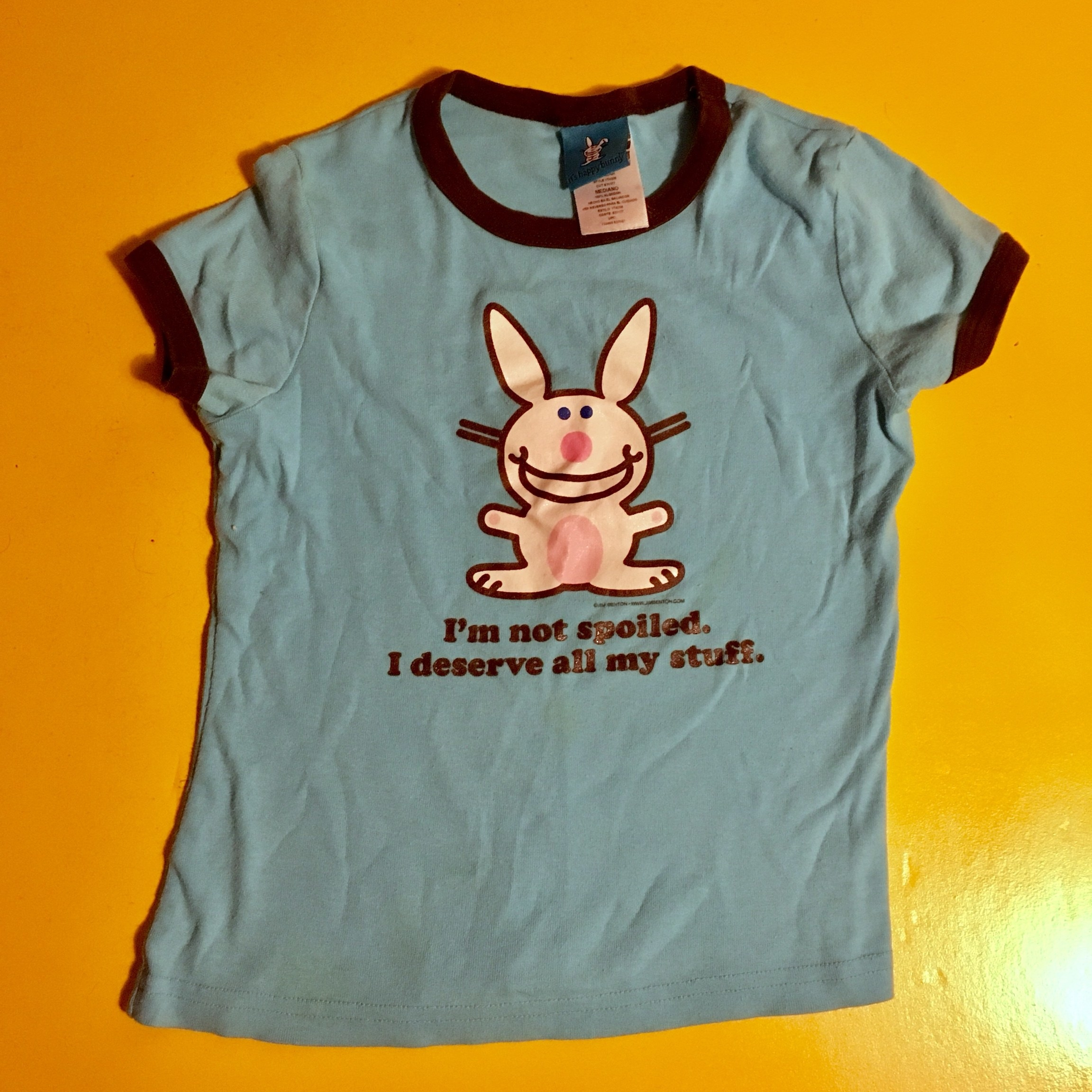 """A blue T-shirt with a bunny on it that with """"I'm not spoiled. I deserve all my stuff"""" written on it"""