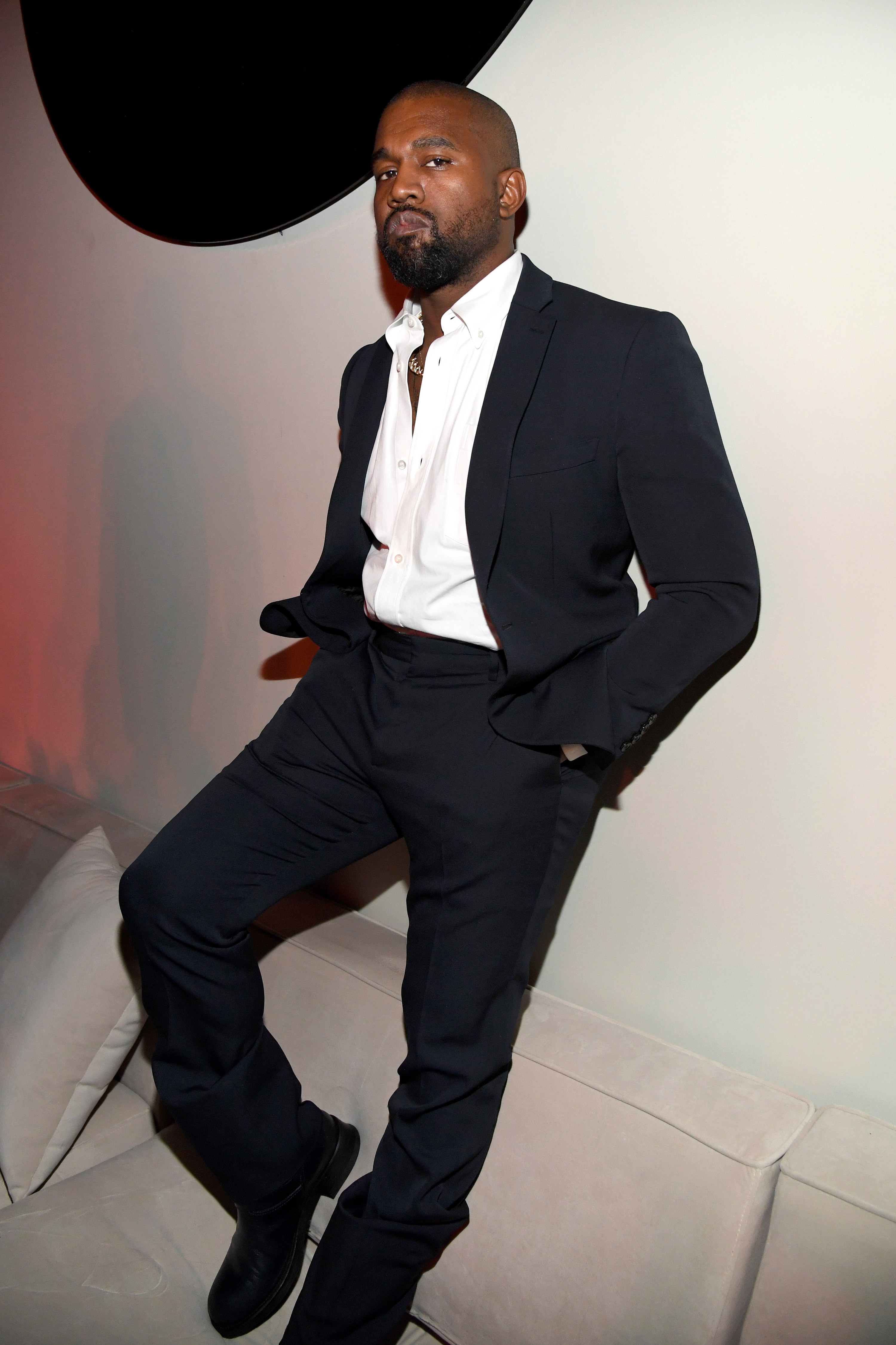 West stands on a couch while leaning against a wall and dressed in a suit
