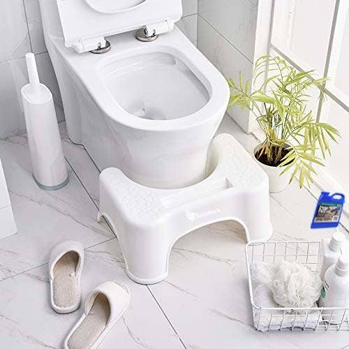 A squat step stool kept in front of toilet seat in bathroom