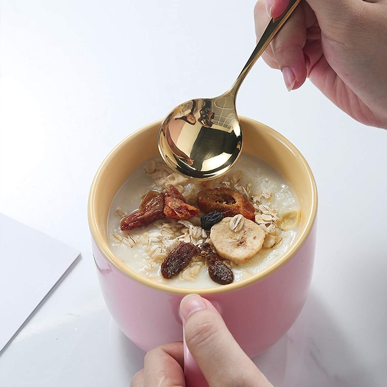 Someone dipping a spoon into the mug; it is filled with oatmeal