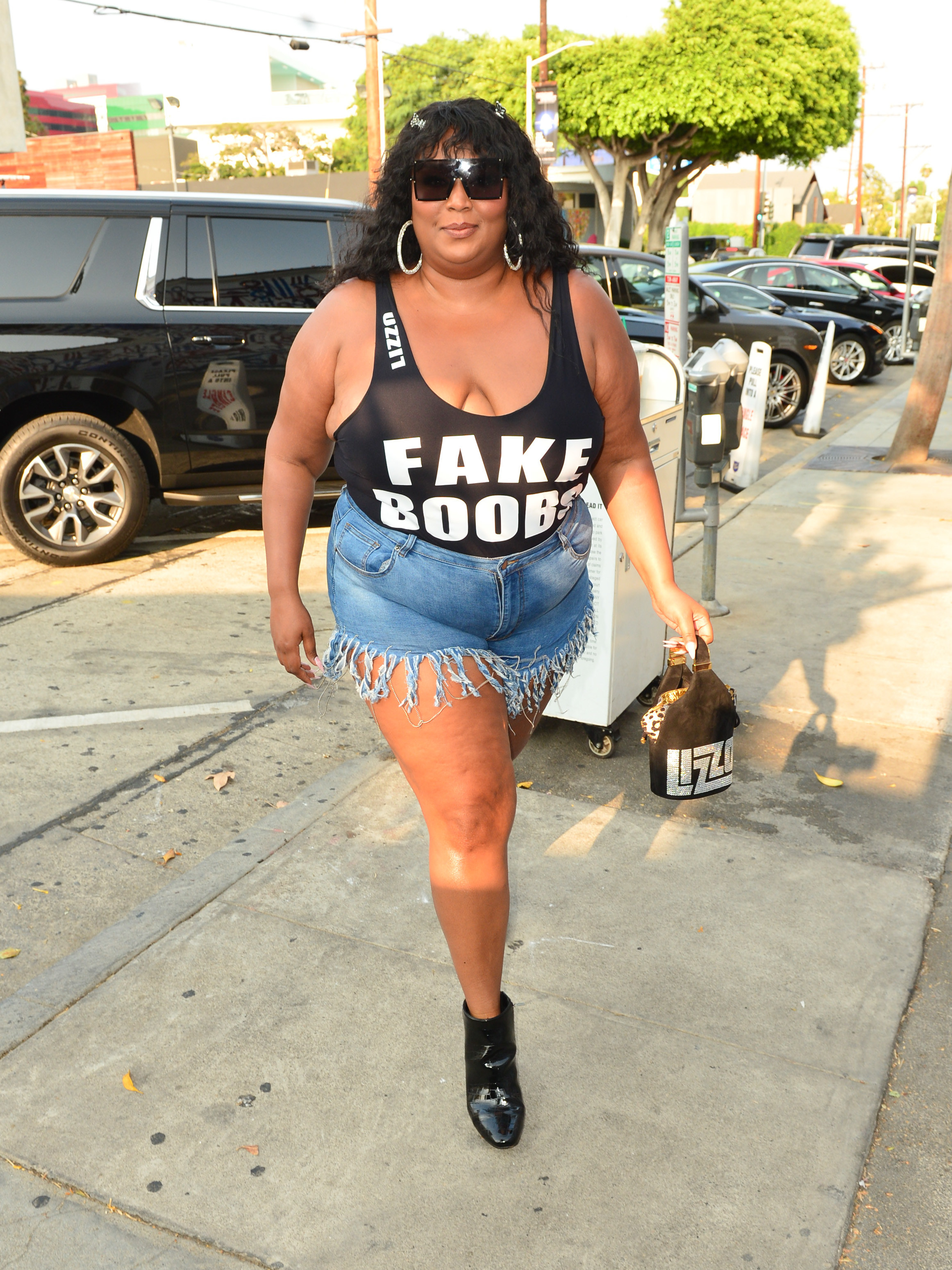 Lizzo walking outside in denim shorts, ankle boots, and a tank bodysuit that says Fake Boobs