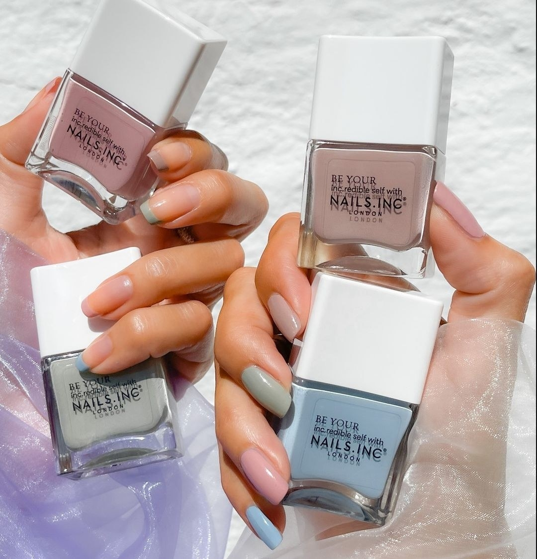A pair of hands holding up all four shades of the vegan nail polishes