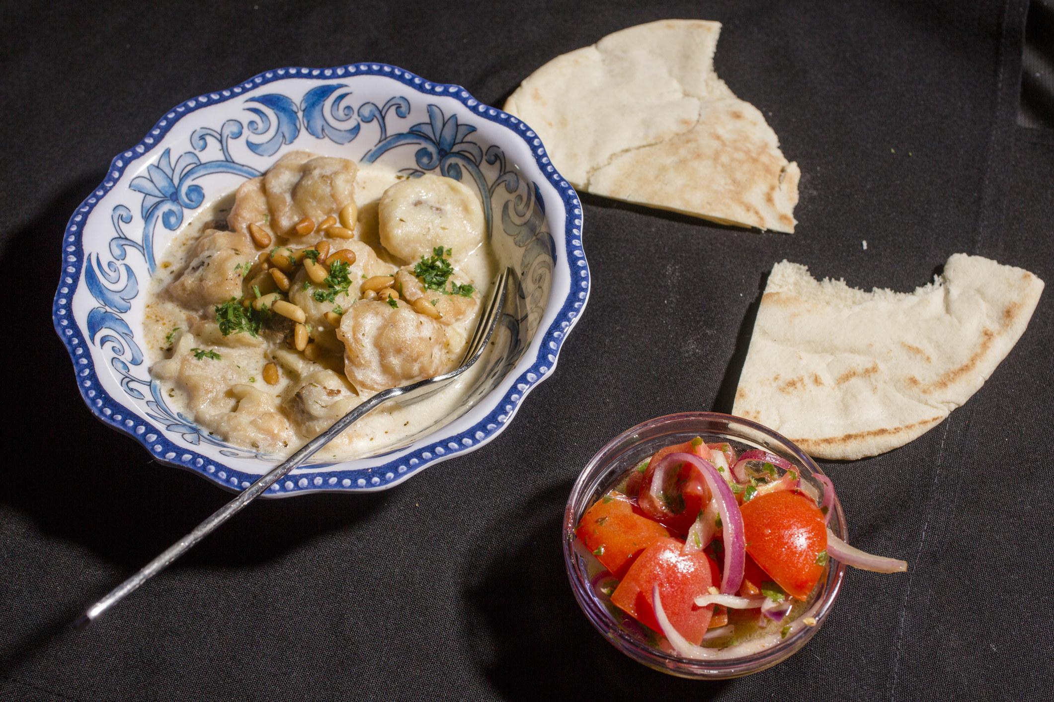 Lebanese shish barak with tomato salad and pita.