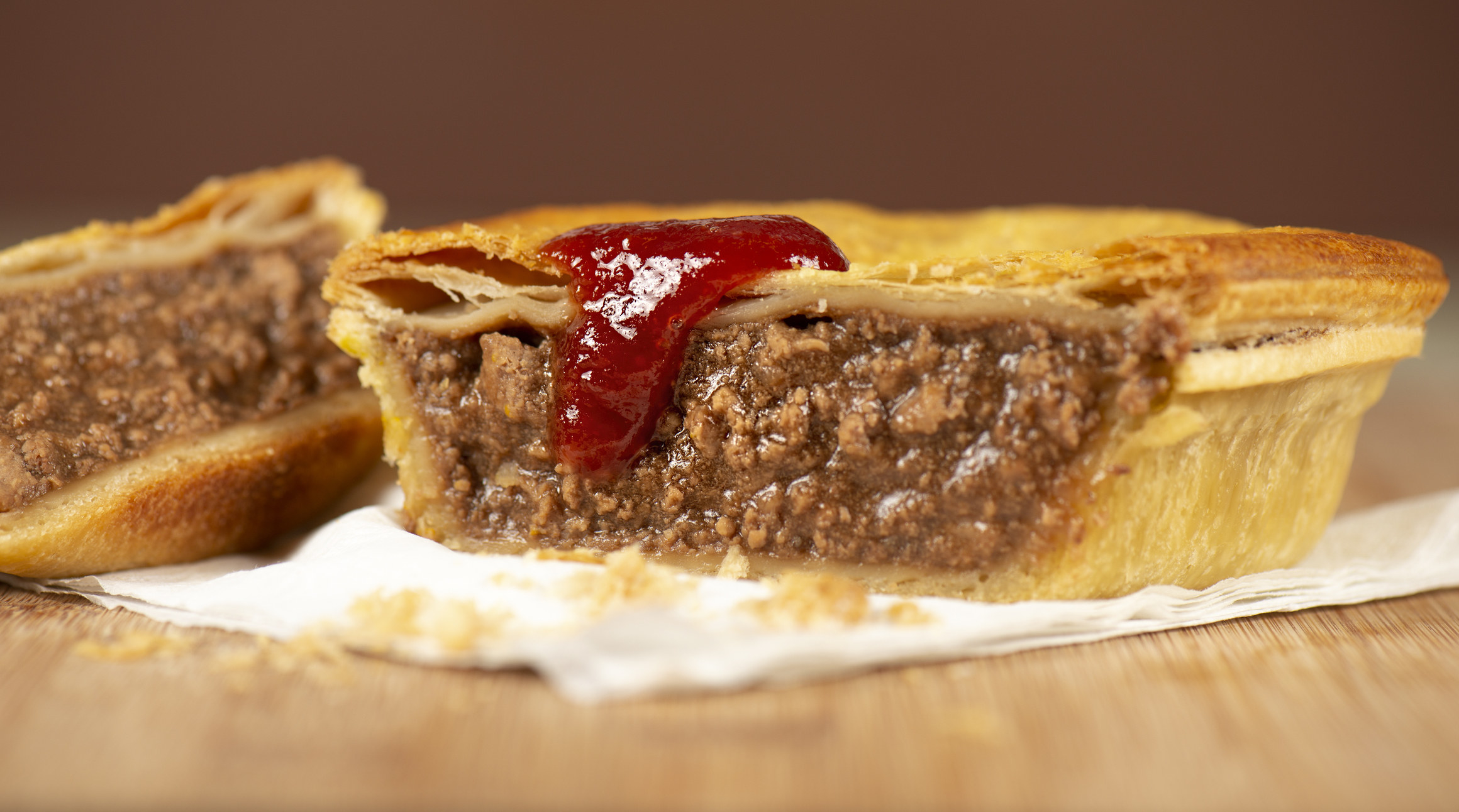 An Australian meat pie with tomato ketchup.