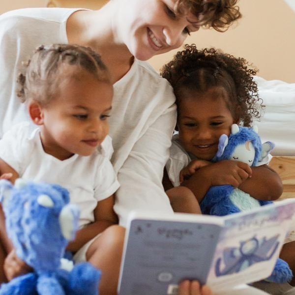 children hugging plush dragons and reading a book