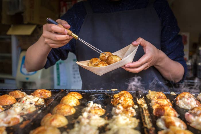 A street vendor cooking tatoyaki.